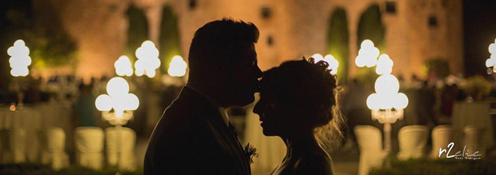Contraluz de novio besando en la frente a la novia con el Castillo de la Arguijuela (Cáceres) al fondo